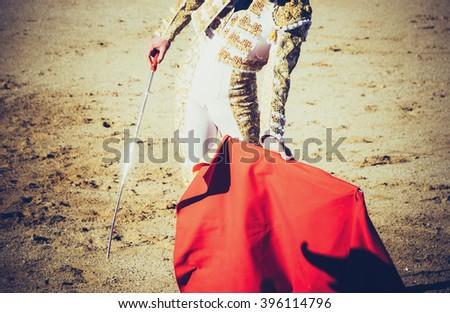 A bullfighter with estoque and muleta giving a pass in the bullring. Corrida de toros. Vignette effect - stock photo