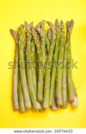 A bunch of asparagus isolated on a yellow background.