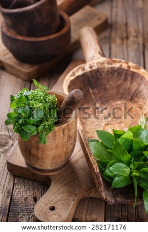 A bunch of Basil in an old bowl. Wooden old kitchenware.selective focus