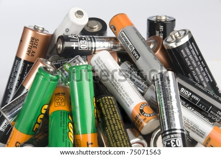 A bunch of batteries piled up disorderly for disposal. Isolated on white background. - stock photo
