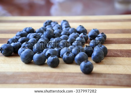 A bunch of blueberries on a cutting board ready to become part of a healthy nutritious snack.