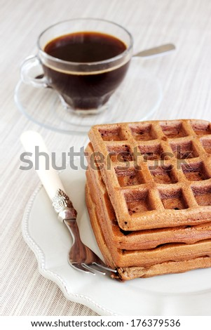 A bunch of chocolate gold brown waffles on light pastel vintage plate and natural napkin. Served with a transparent cup of coffee.
