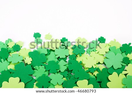 A bunch of colorful shamrocks (four leaf clover) create a festive St. Patricks Day border. NOTE: shamrocks are foam cutouts and have a texture to them. It is not noise.