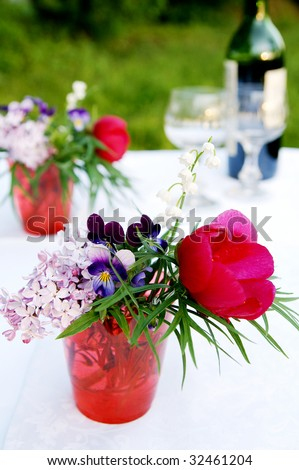 A bunch of different multicolor summer flowers - pansy, lilac, lily-of-the-valley, peony - in a red glass, arranged for picnic table decoration, closeup, vertical - stock photo