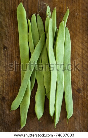 A bunch of flat beans on a wooden board. - stock photo