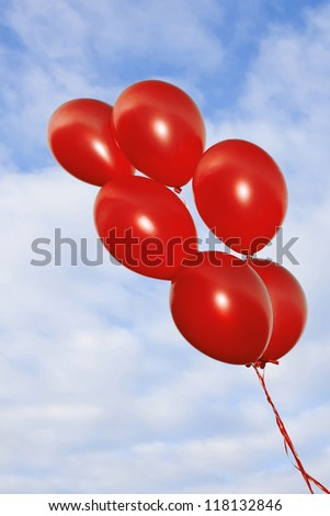 A bunch of flying red balloons on the beautiful sky background - stock photo