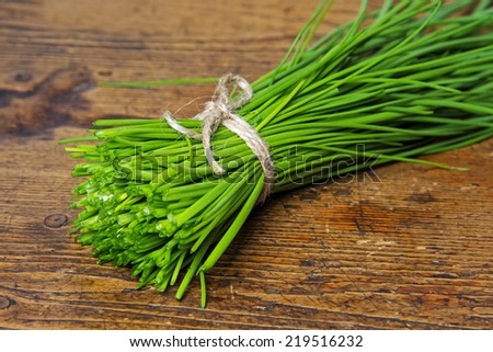 a bunch of fresh chives on a wooden table - stock photo