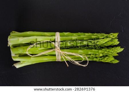 A bunch of fresh green Asparagus on Slate.  - stock photo