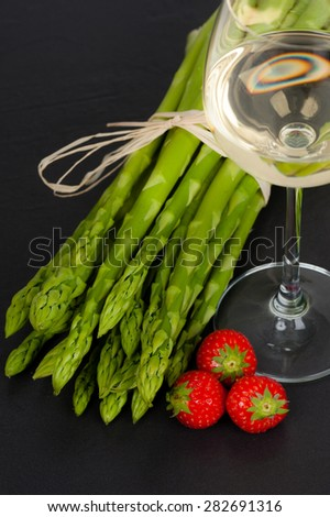 A bunch of fresh green Asparagus on Slate, with a glass of White Wine and Strawberries - stock photo