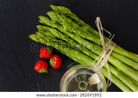 A bunch of fresh green Asparagus on Slate, with a glass of White Wine and Strawberries. - stock photo