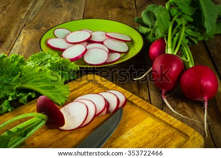 A bunch of fresh radishes, lettuce leaves, slices of radish and knife on old chopping board/ Healthy eating, fresh ripe raw vegetables, diet vegetarian, vegan, vegetable salad. Vegetables. Radishes  - stock photo