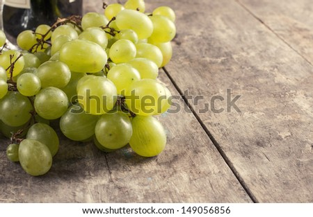 A bunch of green grapes  on old wooden table