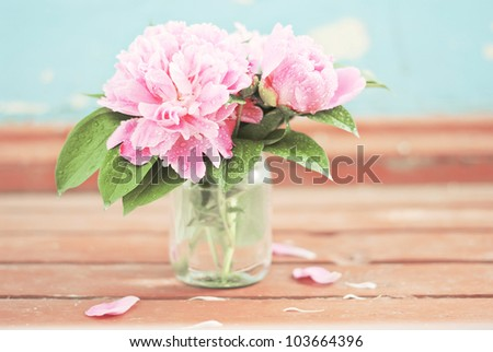 A bunch of pastel pink peony with green leaves on the wooden floor  with a blue background