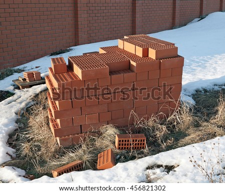 A bunch of red ceramic hollow bricks against a brick fence in the winter. They piled into a briquette