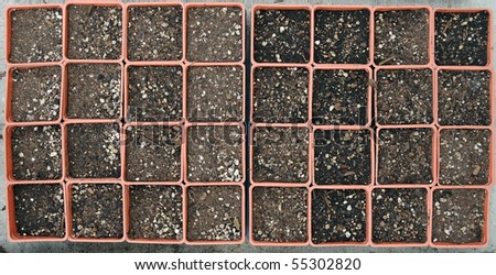 A bunch of small empty gardening pots with soil in each one. - stock photo