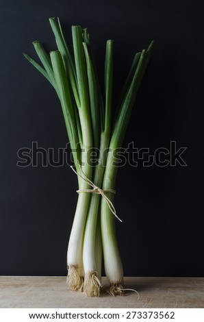 A bunch of spring onions (scallions) tied with string and standing upright on a scratched and worn wooden surface against a black chalkboard background. - stock photo