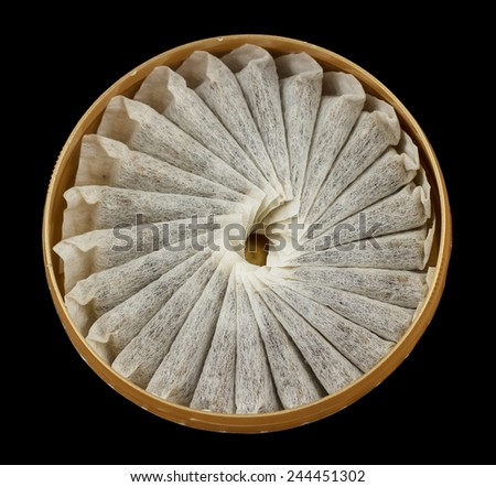 A bunch of swedish snus in a round container isolated on black - stock photo