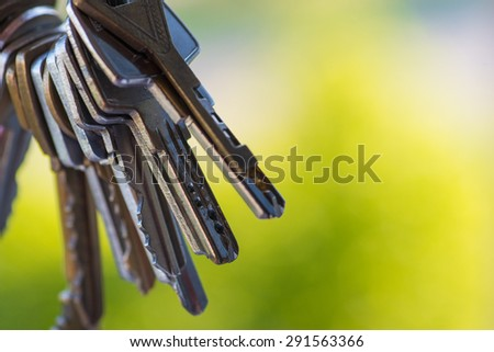A bunch of vintage keys over the open window with green background - stock photo