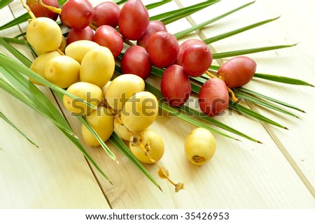 A bunch of yellow and red raw dates with palm leaf - stock photo