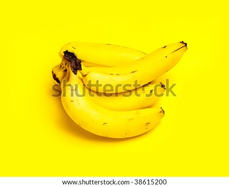 A bunch of yellow bananas isolated on a yellow background.