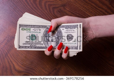 a bundle of money in a female hand with red nails, greed for money,  hundred dollar bills front side, old hundred-dollar bil face, female hand holding pack of money, millionaire - stock photo