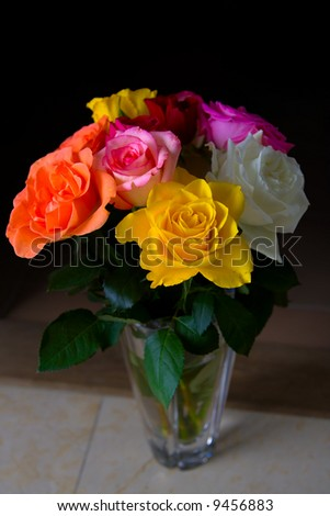 A bundle of roses in a vase with dramatic lighting - stock photo