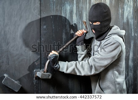 a burglar breaking open of a padlock metal door - stock photo