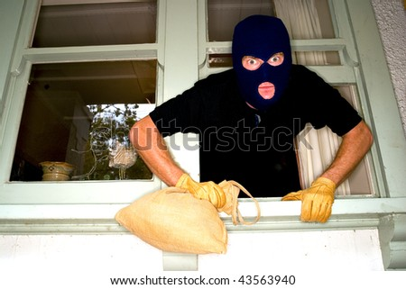 A burglar robbing a house wearing a balaclava. - stock photo