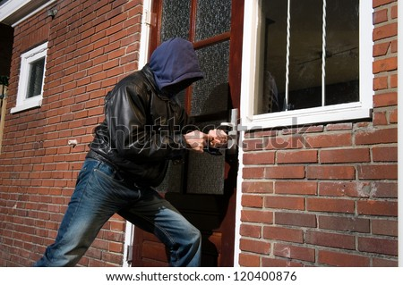A burglar trying to get into a house by the backdoor - stock photo