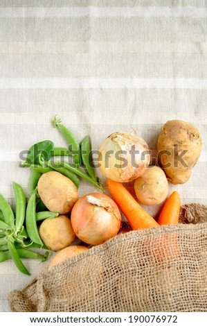 A burlap bag with peas, potatoes, onions and carrots. - stock photo