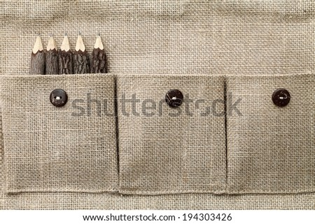A burlap pencil holder filled with wooden pencils - stock photo