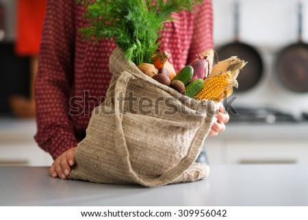 A burlap sac is bursting forth with a selection of autumn vegetables, including corn, cucumbers, onions, and carrots. The possibilities are endless... - stock photo