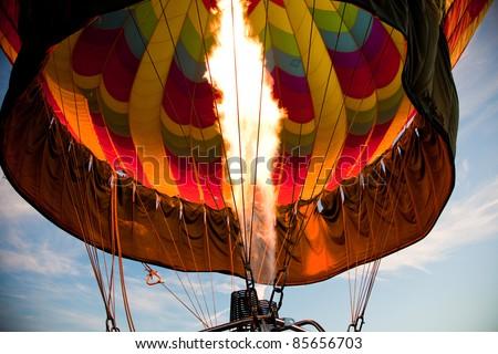A burner with its super hot flame light up the inside of a colorful hot air balloon as it is inflated for an early morning flight. - stock photo