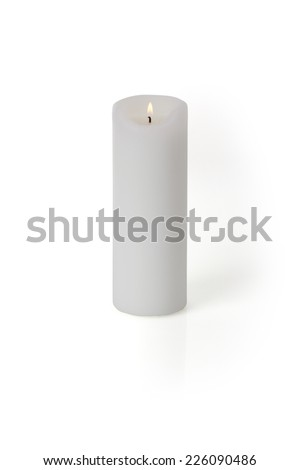 A burning candle isolated on white background with light shaddow and reflection