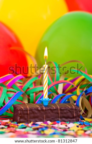 a burning candle on a small cake with streamers and balloons - stock photo