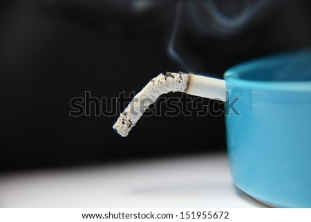 A burning cigarette in the ashtray with a large part of the hanging ash. The ash is associated with male health. Smoking - one of the causes of impotence - stock photo