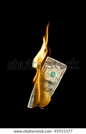 A burning dollar bill symbolizing careless money management - stock photo