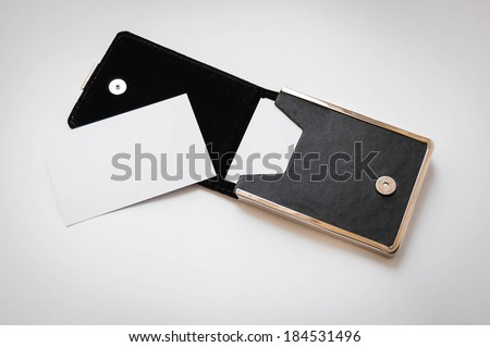 a business card and a black card holder on white background - stock photo