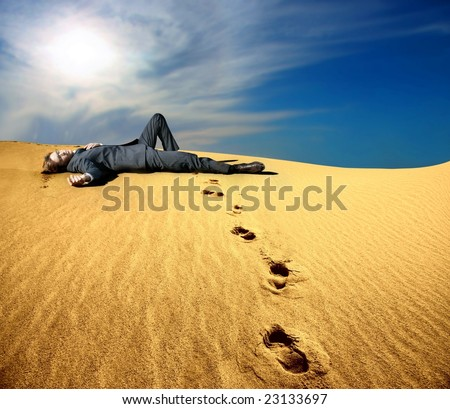 a business dead man in the desert - stock photo