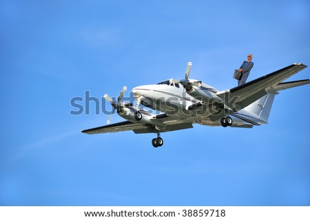 a business executive travels on the wing of a corporate business aircraft - stock photo