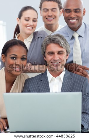 A business group showing ethnic diversity working at a laptop in the office