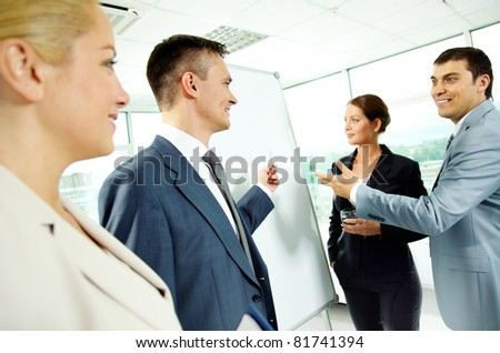 A business man and his partners discussing something on a whiteboard