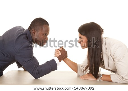A business man and woman arm wrestling with serious expressions on their faces. - stock photo