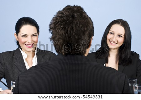 A business man back having a job interview with two business women and they laughing together - stock photo