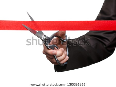 A business man cutting a scarlet ribbon with scissors, isolated on white - stock photo