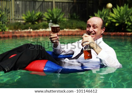 A Business man floating in a swimming pool, having just cracked the first beer of the day, still dressed in his business attire. - stock photo