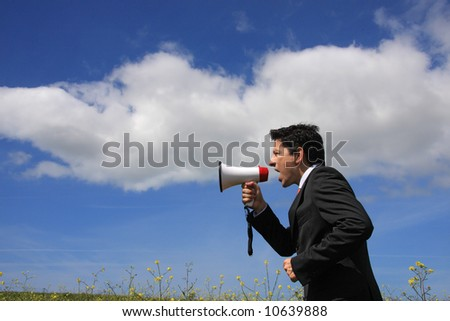 A business man giving an order with a megaphone - stock photo
