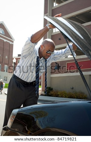 A business man having a bad day checks under the hood of his car to figure out what the problem is. - stock photo