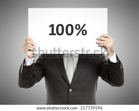 A business man holding a paper in front of his face with the text 100%