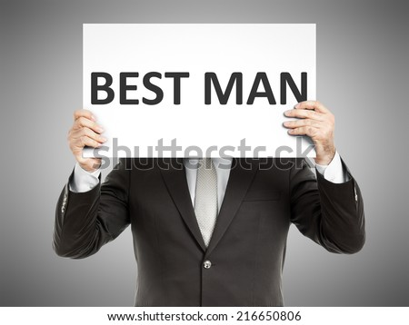 A business man holding a paper in front of his face with the text best man - stock photo
